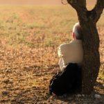 homme seul au pied d'un arbre dans un champ regardant l'horizon